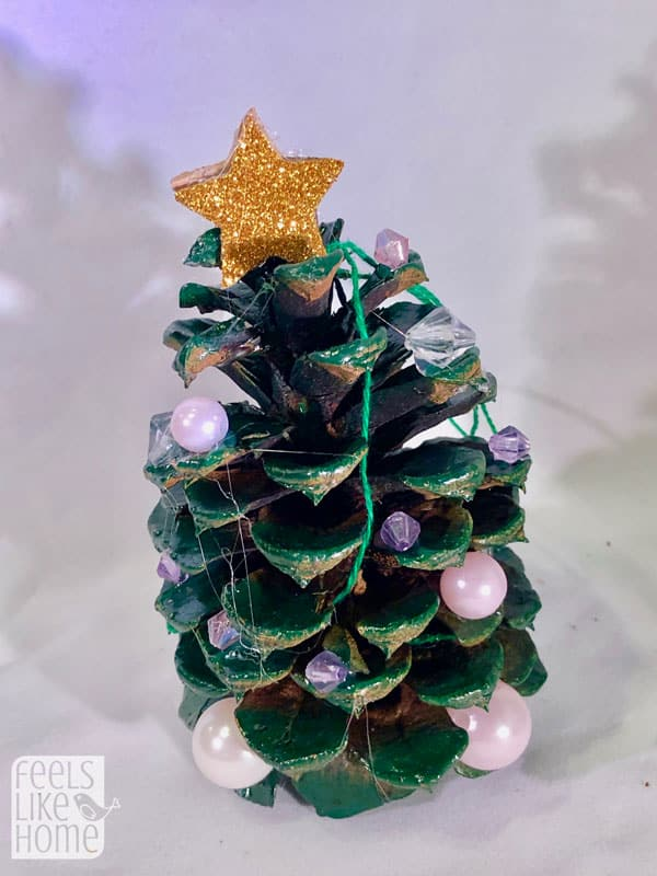 A close up of a pine cone Christmas tree with beads for ornaments