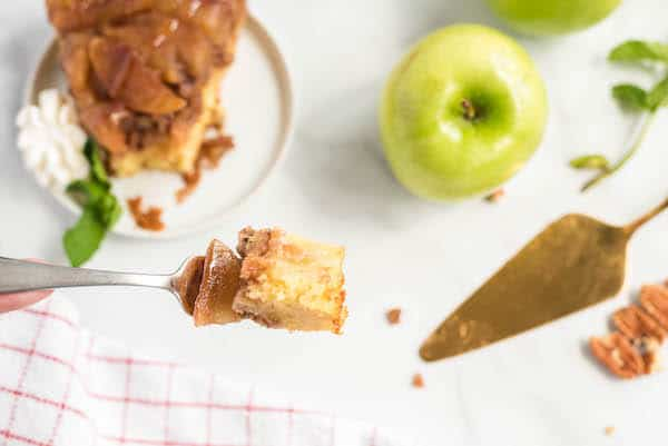 one bit of upside down cake with apples in the background
