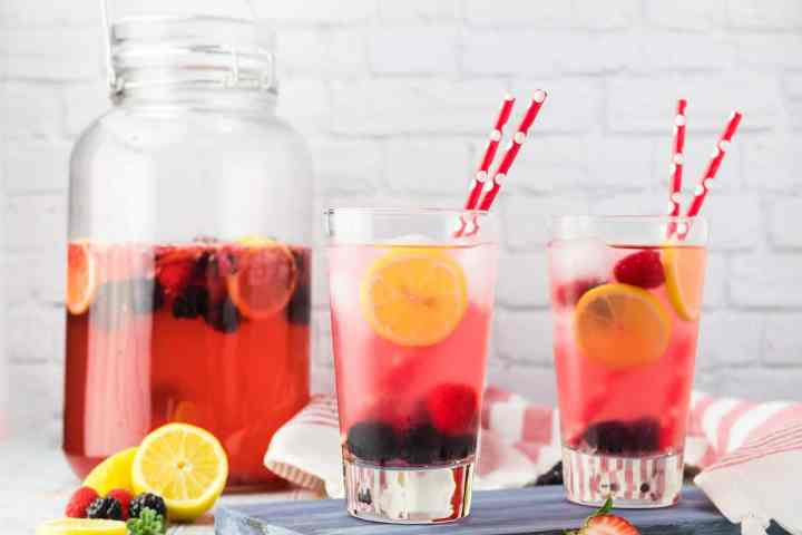a pitcher of berry lemonade and two glassess