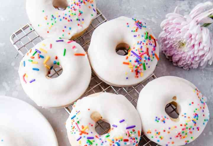 baked vanilla cake donuts with white frosting and colored sprinkles