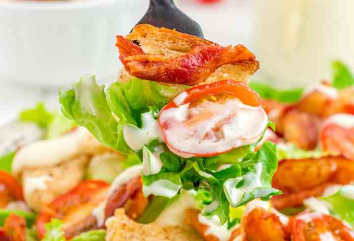 one bite of BLT salad with bacon, tomatoes, lettuce, and a bacon rye crouton