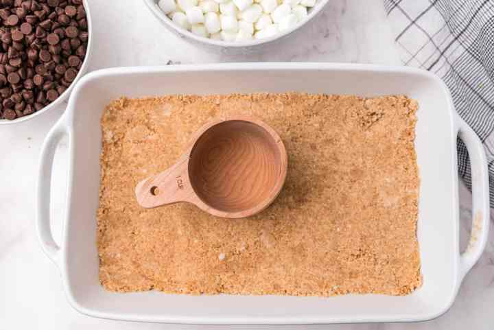 press the graham cracker cookie mixture into the pan