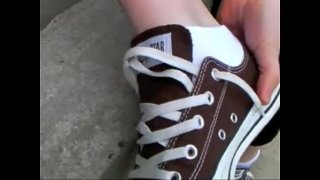 Young Girl Wearing Black Converse Slowly Taking Off Her Shoes And Socks