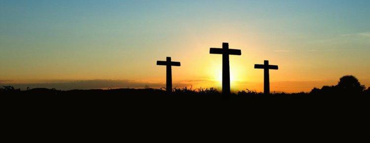 3 Kreuze auf einem Hügel vor der untergehenden Sonne