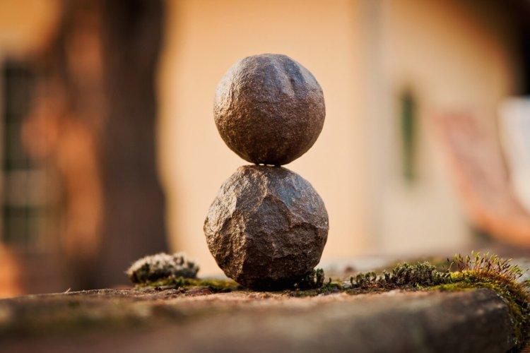 """Symbolbild """"Heilung der Seele durch Seelsorge"""": 2 Steine in Balance aufeinander"""
