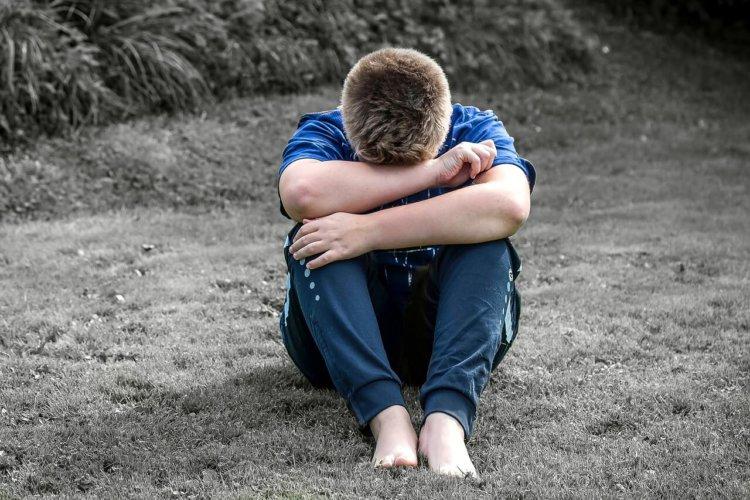 """Symbolbild """"Schäm dich nicht!"""": Zusammengekauerter Junge auf einer Schwarz-weißen Wiese"""