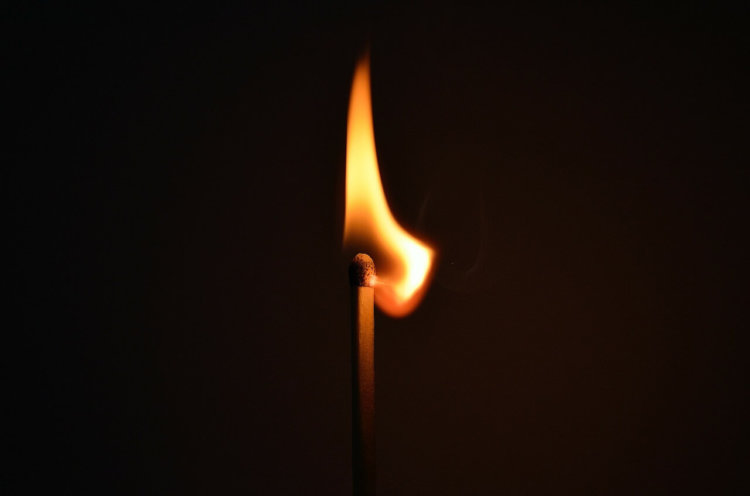 """Symbolbild """"Licht in der Dunkelheit"""": Nahaufnahme brennendes Streichholz"""