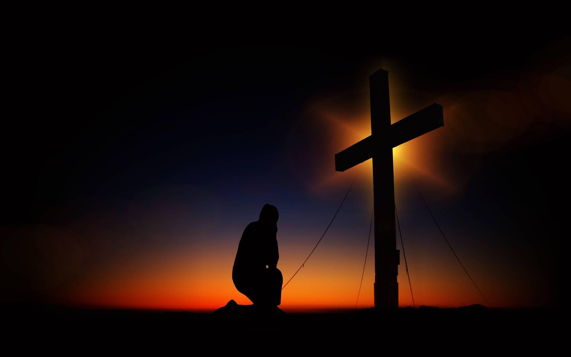Symbolbild Demut: Mann kniet vor Kreuz bei Sonnenuntergang