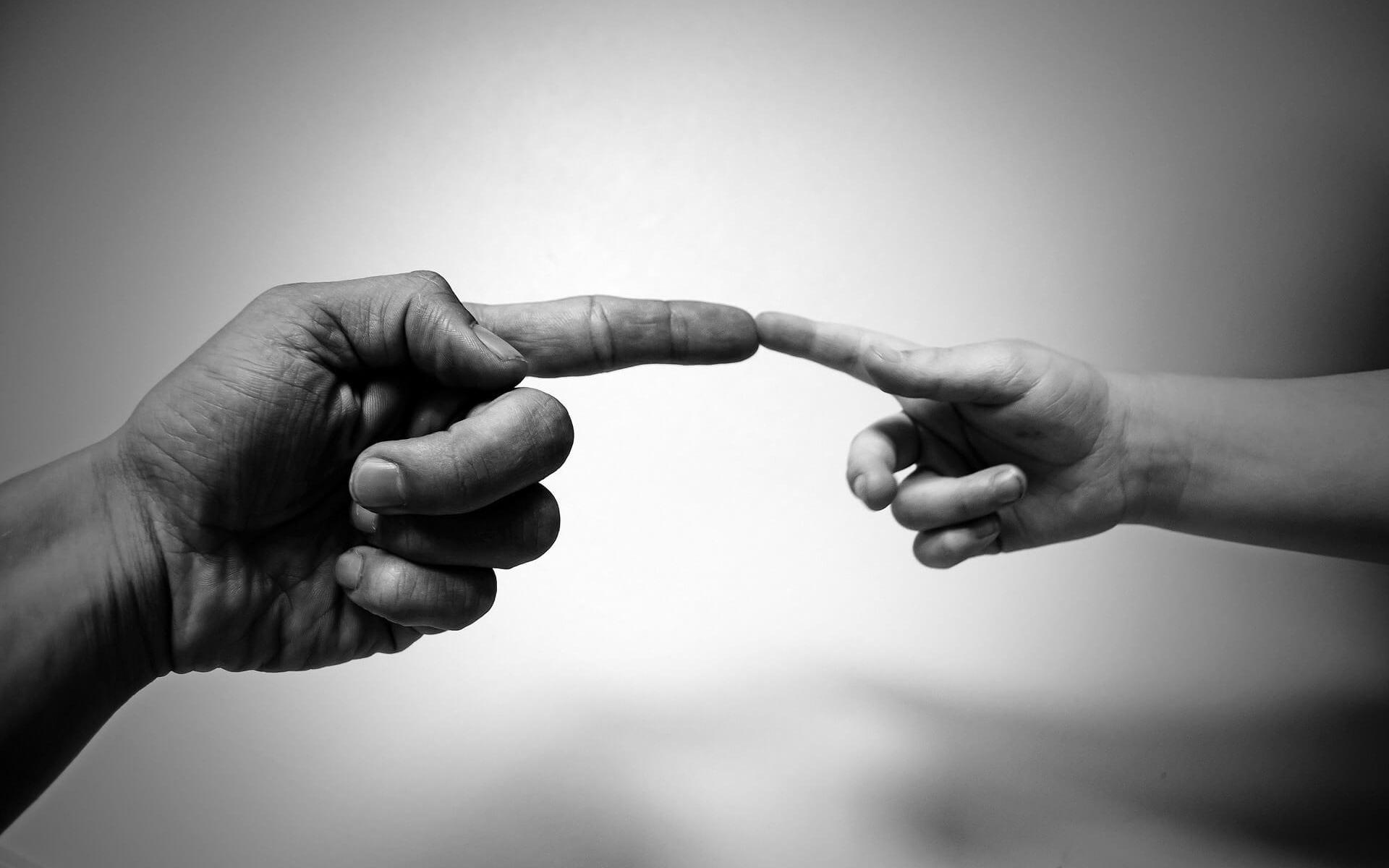 Gott schuf den Menschen zu seinem Bilde. Bild große Hand mit Finger an kleiner Hand
