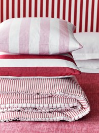 Quilt in Ticking Peony 01 £24.50 per metre, cushions in Ticking Pink 02 £24.50 per metre and Devon Stripe Peony £24.50 per metre - all Ian Mankin