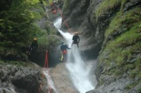 Wildwasserretter seilen sich im Wasserfall ab. Fachbereich Wildwasser - Canyoning