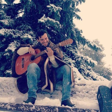 Felipe Alberto playing guitar in the snow