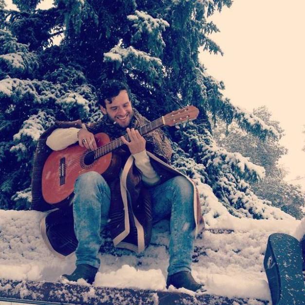 Felipe Alberto playing guitar in the snow