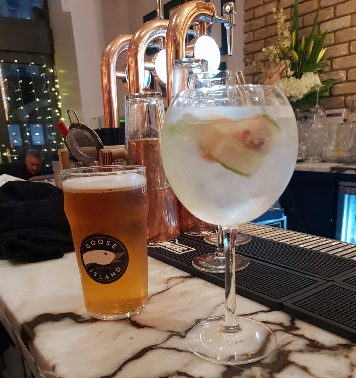 A balloon glass of Hendricks Gin and Fever Tree tonic and a pint glass of Goose Island IPA sitting on a marble bar. Castle Street Townhouse, Liverpool - Female Original