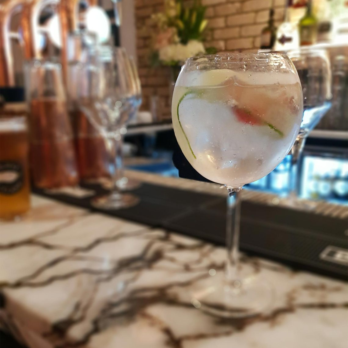 A balloon glass of Hendricks Gin Fever Tree tonic sitting on a marble bar. Castle Street Townhouse, Liverpool - Female Original