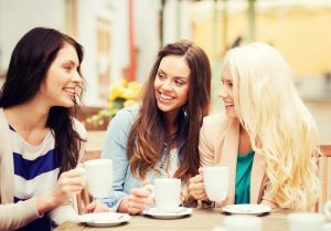 holidays and tourism concept - beautiful girls drinking coffee i