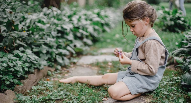 cute stylish child playing with chalks in the garden t