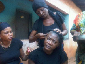 Women shaving a widow's hair