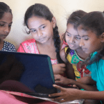 A group of girls are sitting around a laptop