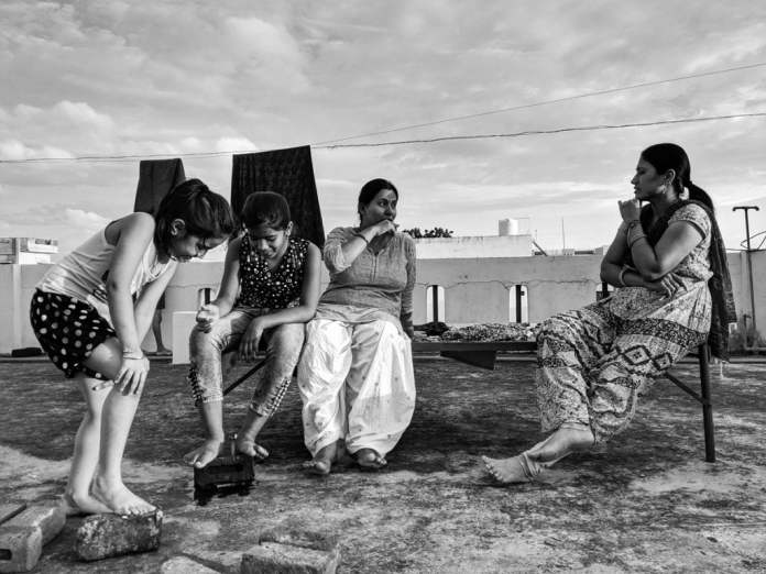 Women at Leisure: Sushma and Aasha enjoy a break on Sushma's terrace before they both return to their kitchens to prepare dinners for their families. Their daughters are enjoying each other's company.