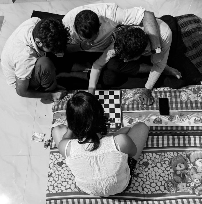 Women at Leisure: Zeba is playing chess against three of her friends.