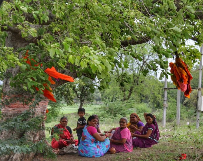 Women at Leisure: A group of women on a religious outing to a sacred tree outside their village. After finishing their prayers/Pooja, they sat together to catch-up.