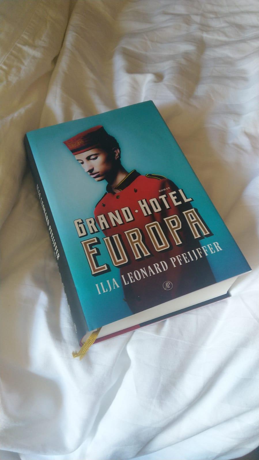 Het boek Grand Hotel Europa neergelegd op een bed met witte lakens.