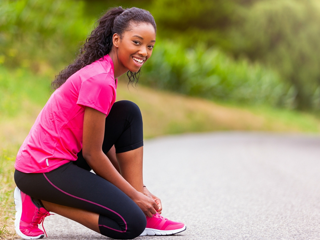Fit woman tying sneakers - 5 Ways To Achieve Fitness Goals