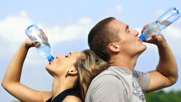 Couple drinking bottled water