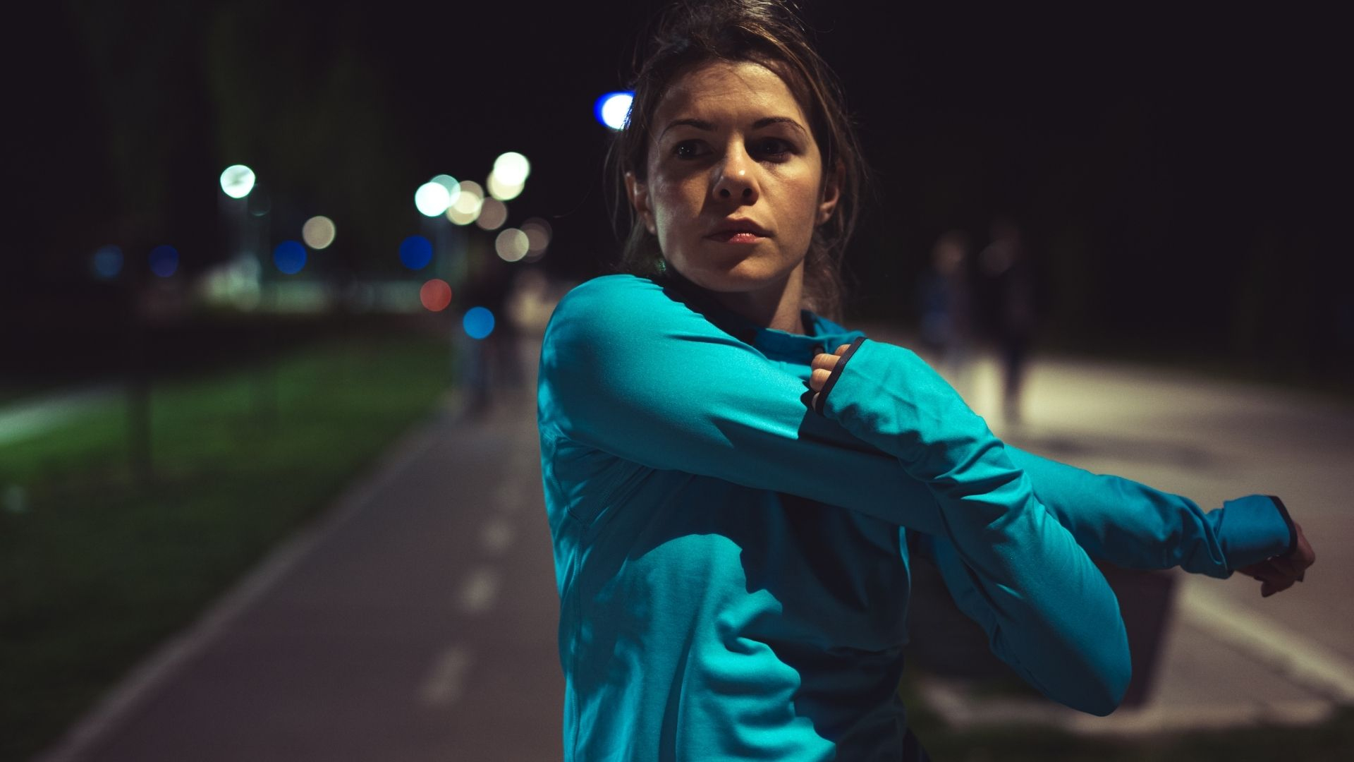 Runner stretching preparing to run in the dark outdoors
