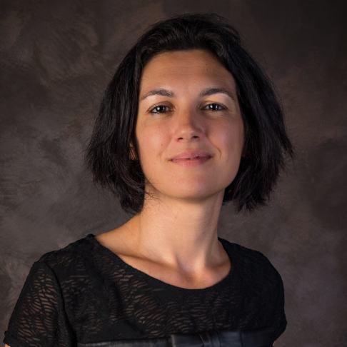 Image de Lucie Rondelet habillée en noir et elle fixe l'objectif avec un  visage légèrement souriant.