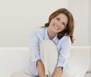 Smiling mature woman sitting on her couch