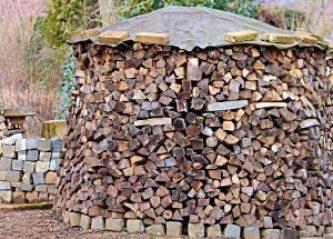 bois de chauffage rangé en rond avec bâche