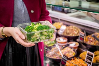 someone holding a clear plastic container full of green vegetables