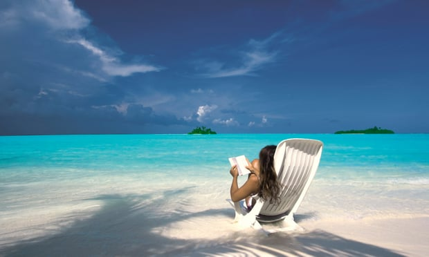 woman reading book on a pristine white beach