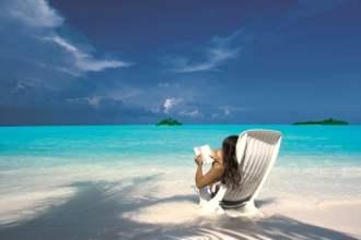 woman reading book on a pristine white beach