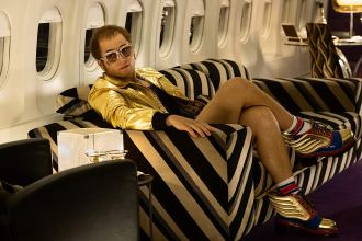 taron egerton as elton john, lounging in a private jet and wearing lots of gold