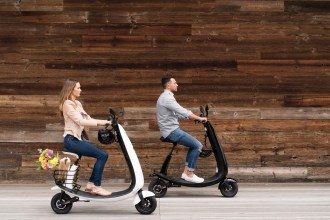 OjO commuter scooter - two people riding scooters past a wooden wall