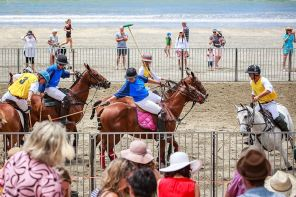 teams of blue and yellow verse off in a game of beach polo