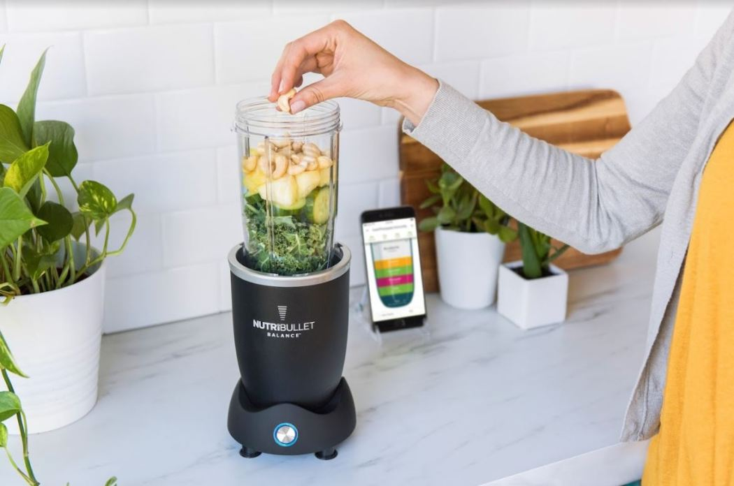woman placing bananas in a nutribullet, with the nutribullet app open next to it