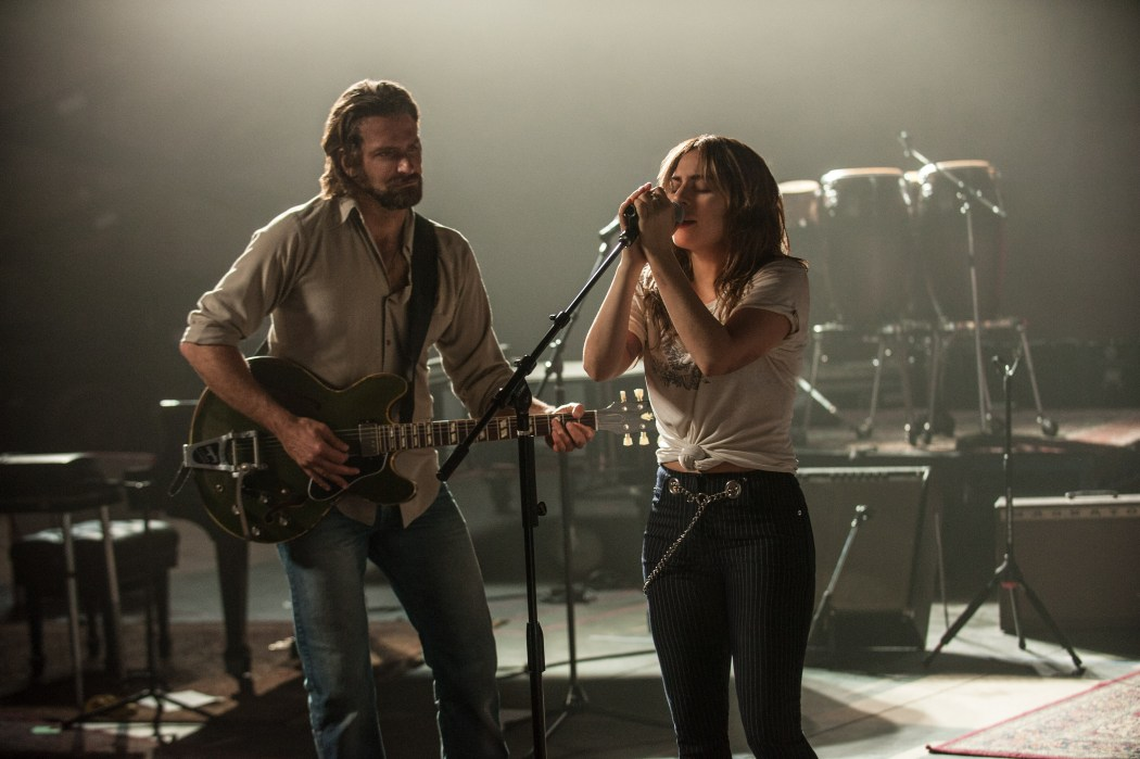 still from a star is born. ally sings into a microphone while jackson plays guitar and gazes fondly at ally