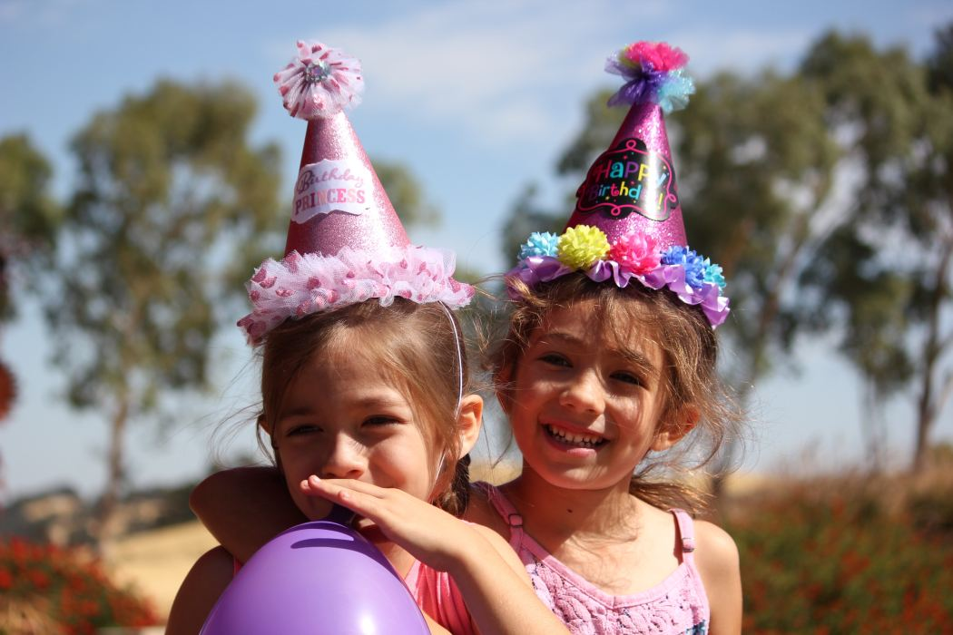 Two kids with party hats on