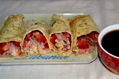 An omelette roll with ham, cheese and tomato cubes inside