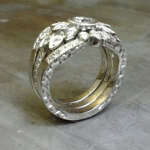 intricate thick custom engraved band with round center diamond and surrounding marquise diamonds in a flower setting side view