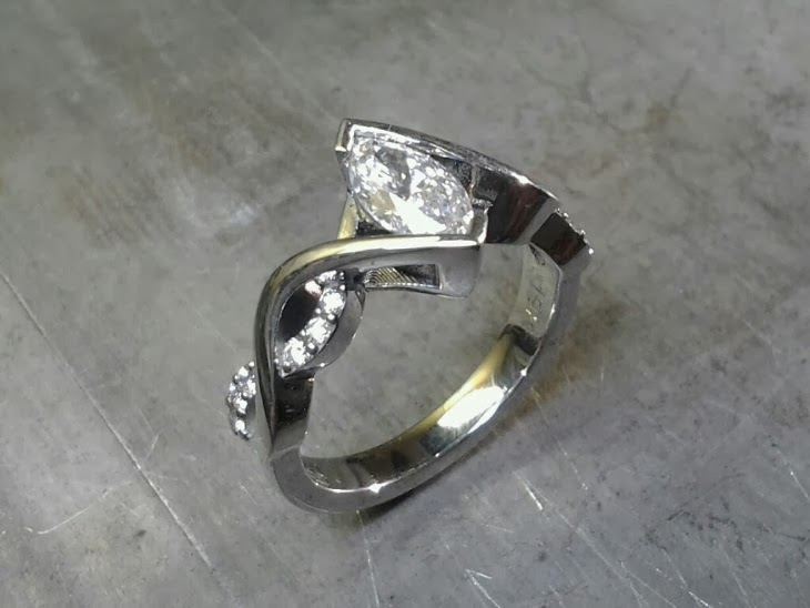 infinity white gold band engagement ring with diamonds and marquise tension set center diamond side view