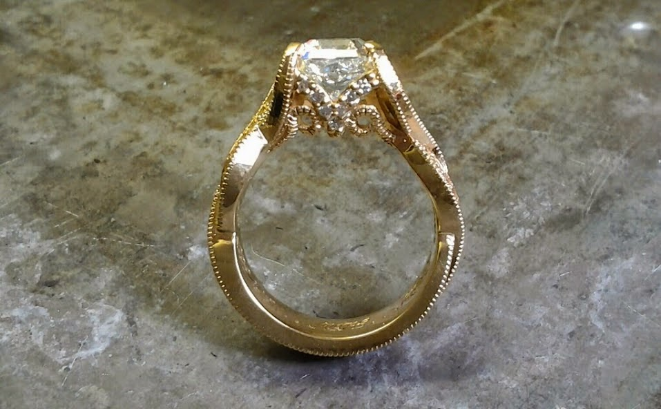 gold intricate engagement ring with princess cut diamond floating in channel setting side view