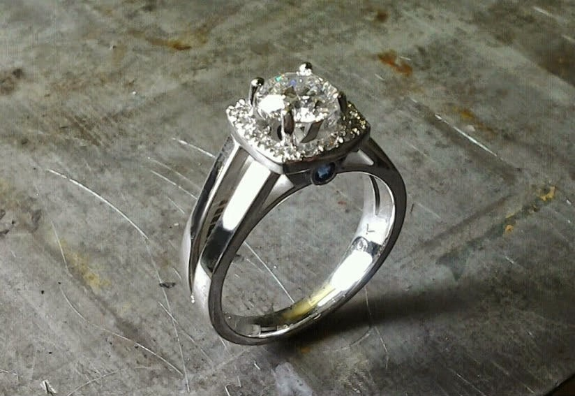 simple split white gold band with large round diamond and diamond halo setting