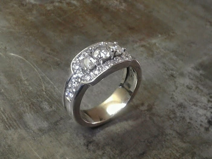 custom designed white gold engagement ring with three large diamonds surrounded by smaller ones