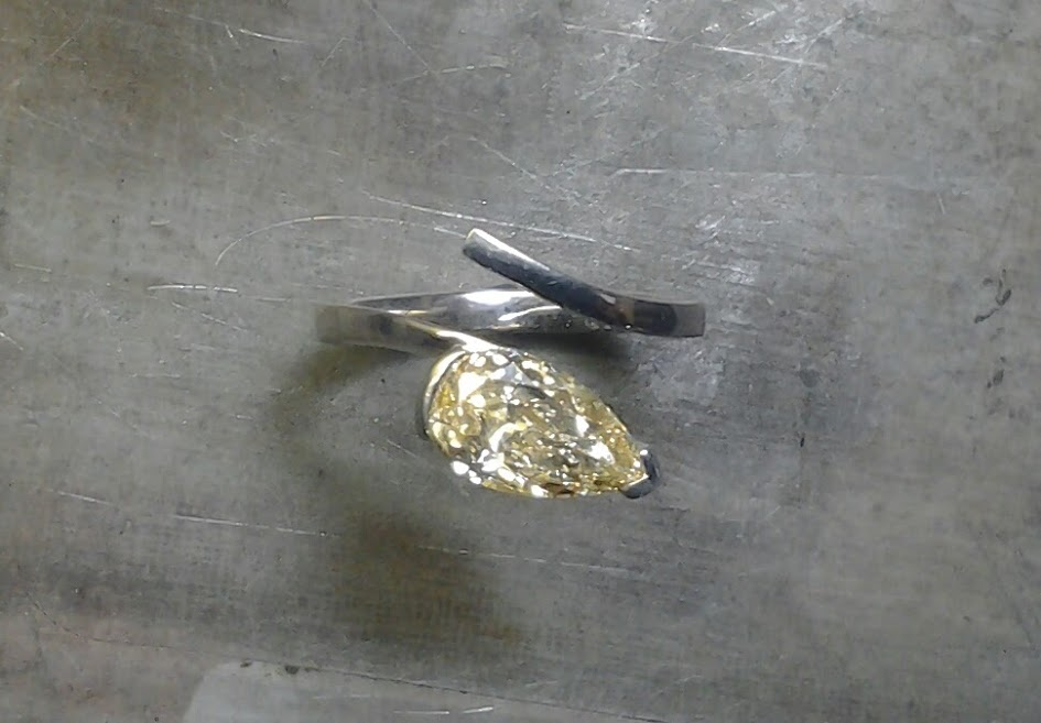 pale yellow teardrop diamond and unique open-style band