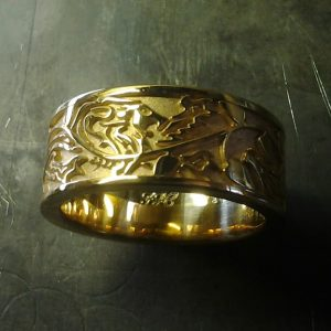 custom gold wedding band with lion engraving